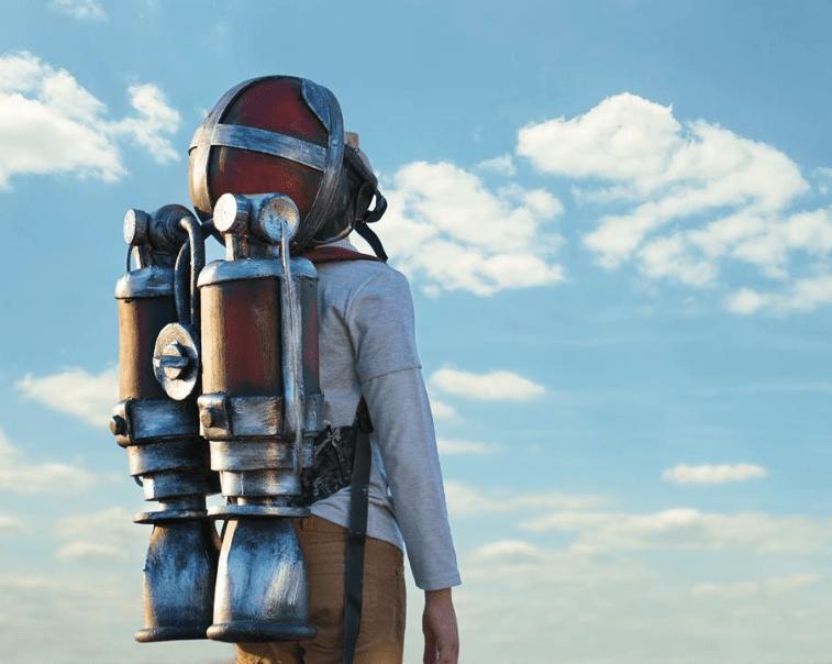 Un niño con un cohete en la espalda mira al cielo