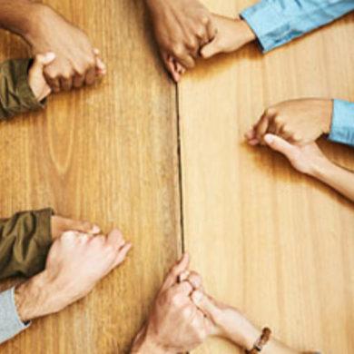 Manos juntas de varias personas en sentido de oracion común dentro de un colegio concertado en madrid.